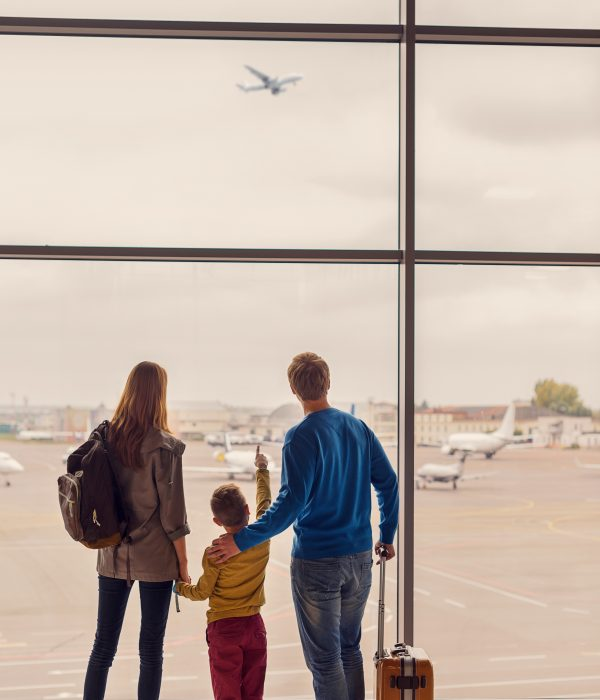 Look dad. Back view shot of little boy and his parents waiting at airport for departure and pointing with finger on plane