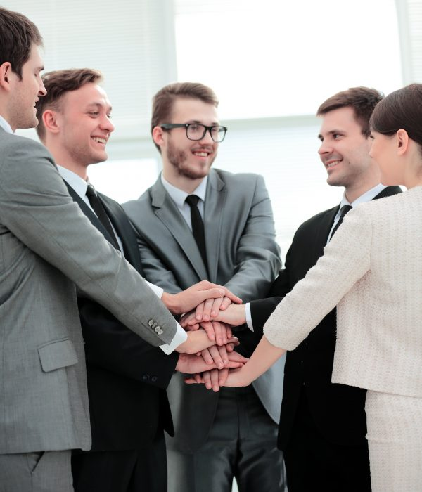 closeup-business team welcomes new employees and stands with hands clasped together. the photo has a empty space for your text